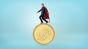 A businessman in a red superhero cape balancing on the edge of a giant golden coin with a USD sign. Money and investment. Financial wisdom. Business risks royalty free stock photo
