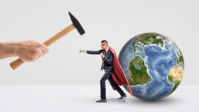 A businessman in a red superhero cape protecting a small globe behind him and punching a giant hand holding a hammer. International business. Corporate hero Stock Photography