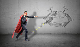 A businessman in a red superhero cape throwing punches at a wall drawing of an UFO striking at him. Business troubles. Unexpected competition. Consulting and royalty free stock photography