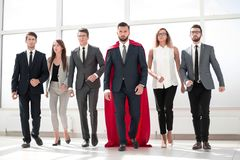 Businessman in a red superhero cloak and his business team stock photos