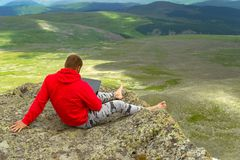 Businessman in a red sweatshirt is sitting on a rock on a mounta royalty free stock photography