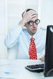 Businessman with a red tie and a blue shirt has made a mistake -. Touching his head at desk looking in his computer Stock Image