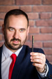 Businessman in red tie is looking at the pen Stock Photos