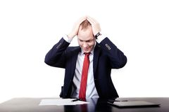 Businessman in red tie at the table took his head Royalty Free Stock Photo