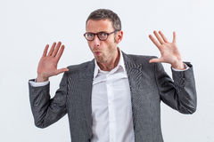 Businessman refusing to be guilty or denying responsibility. Corporate denial concept - carefree 40s businessman with eyeglasses raising his hands refusing to be Stock Photo