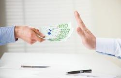 Businessman refusing to take a bribe