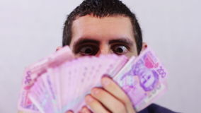 Businessman Rejoices his Money. Businessman counts tens of thousands of Hryvnia (Ukrainian currency), holding them in their hands.  A man dressed in a business stock footage