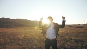 Businessman rejoices and jumps on nature stock video footage