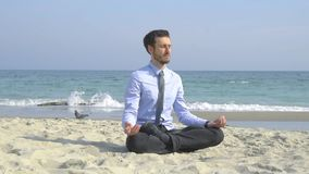 Businessman relax on the beach. Young male businessman relax on the beach in sunny day an do meditation in lotus pose stock video