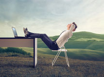 Businessman Relaxing. A businessman is relaxing in a large field of countryside Royalty Free Stock Photos