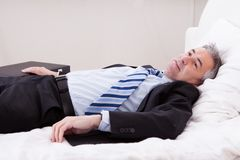 Businessman Relaxing On Bed Royalty Free Stock Photo