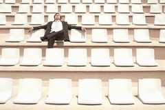 Businessman Relaxing In Center Of Empty Auditorium Royalty Free Stock Images