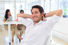 Businessman relaxing with coworkers in background Royalty Free Stock Images