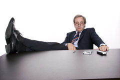 Businessman relaxing at desk. Successfull businessman relaxing over his desk, isolated in white background Royalty Free Stock Photos