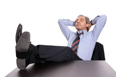 Businessman relaxing at desk. Closeup of mature middle aged businessman sleeping with feet on desk, isolated on white background Royalty Free Stock Images