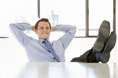 Businessman Relaxing At Desk In Office Stock Photo
