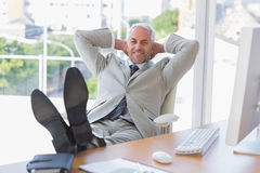 Businessman relaxing at desk and smiling at camera Stock Image