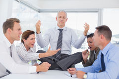 Businessman relaxing on the desk with upset colleagues around Royalty Free Stock Photography