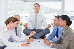Businessman relaxing on the desk with upset colleagues around Stock Photography