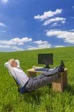 Businessman Relaxing Feet Up Desk in Green Field. Man or male businessman relaxing feet up at a desk with a computer in a green field drinking tea or coffee Stock Photo