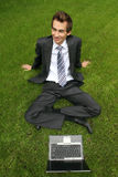 Businessman relaxing on grass with his laptop Stock Image