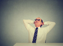 Businessman relaxing at his desk looking up Stock Images