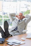 Businessman relaxing at his desk Stock Photos