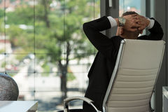 Businessman Relaxing With His Hands Behind His Head Stock Photo