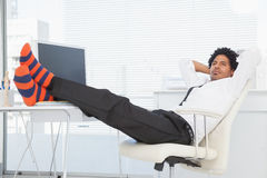Businessman relaxing in his swivel chair with feet up Royalty Free Stock Images
