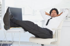 Businessman relaxing in his swivel chair with feet up Stock Images