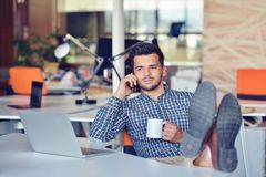 Businessman relaxing with legs up on desk, drinking coffee while dreaming about future at workplace in modern office. Royalty Free Stock Images