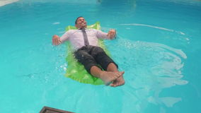 Businessman relaxing on lilo stock video footage