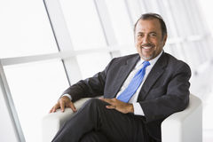 Businessman relaxing in lobby Stock Images