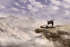 Businessman relaxing on mountain Stock Image