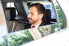 Businessman relaxing with music in a car. Good looking young businessman relaxing in the backseat of a car listening to music with earbuds Stock Images
