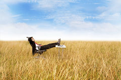 Businessman relaxing outdoor. Portrait of a young businessman sitting relaxed on chair against sky Stock Image