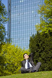 Businessman relaxing in park during lunch break. A businessman relaxing in a park during his lunch break and enjoying the sun Stock Images