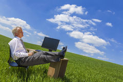Businessman Relaxing Thinking At Desk in Green Field. Man or male businessman relaxing feet up at a desk with a computer in a green field drinking tea or coffee Stock Image