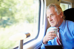 Businessman Relaxing On Train With Cup Of Coffee Royalty Free Stock Photos