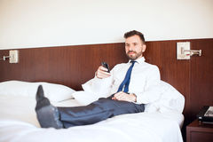 Businessman relaxing and watching TV. Full length view of a young businessman with a beard watching TV in his hotel room during a business trip Royalty Free Stock Photography