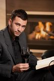 Businessman relaxing after work. Businessman relaxing at home after work, drinking wine, reading book Stock Images