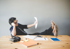 Businessman relaxing and working at desk in creative office stock photos