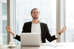Businessman relieves work stress with meditation. Relaxed young entrepreneur meditating at desk in front of laptop. Office worker doing yoga exercises at Stock Photo