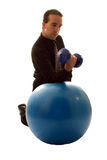 Businessman Relieving Stress. Businessman using a yoga ball and weights to help relieve stress stock images