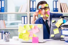 The businessman with reminder notes in multitasking concept. Businessman with reminder notes in multitasking concept stock images