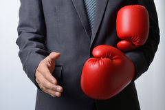Businessman remove boxing gloves to offer a handshake on white b. Businessman remove red boxing gloves to offer a handshake on white background,compromise Royalty Free Stock Photos