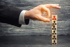 The businessman removes / dismisses the employee from the team. management within the team. wooden blocks with a picture of worker. S. control arm. leader royalty free stock photo