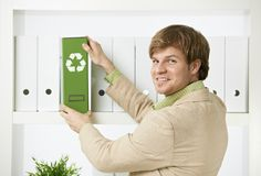 Businessman removing green folder from shelf Royalty Free Stock Photos