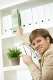 Businessman removing green folder from shelf Royalty Free Stock Images