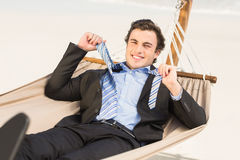 Businessman removing his tie on the hammock Royalty Free Stock Image